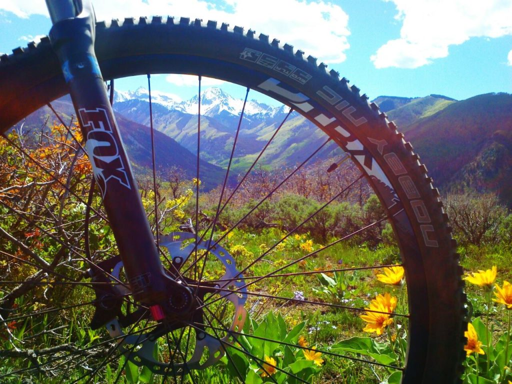 bike wheel up close with mountains in the background