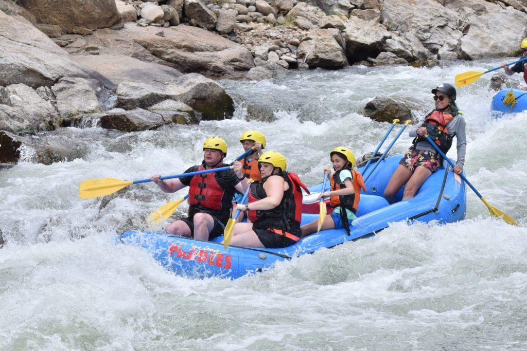 group paddling in rapids
