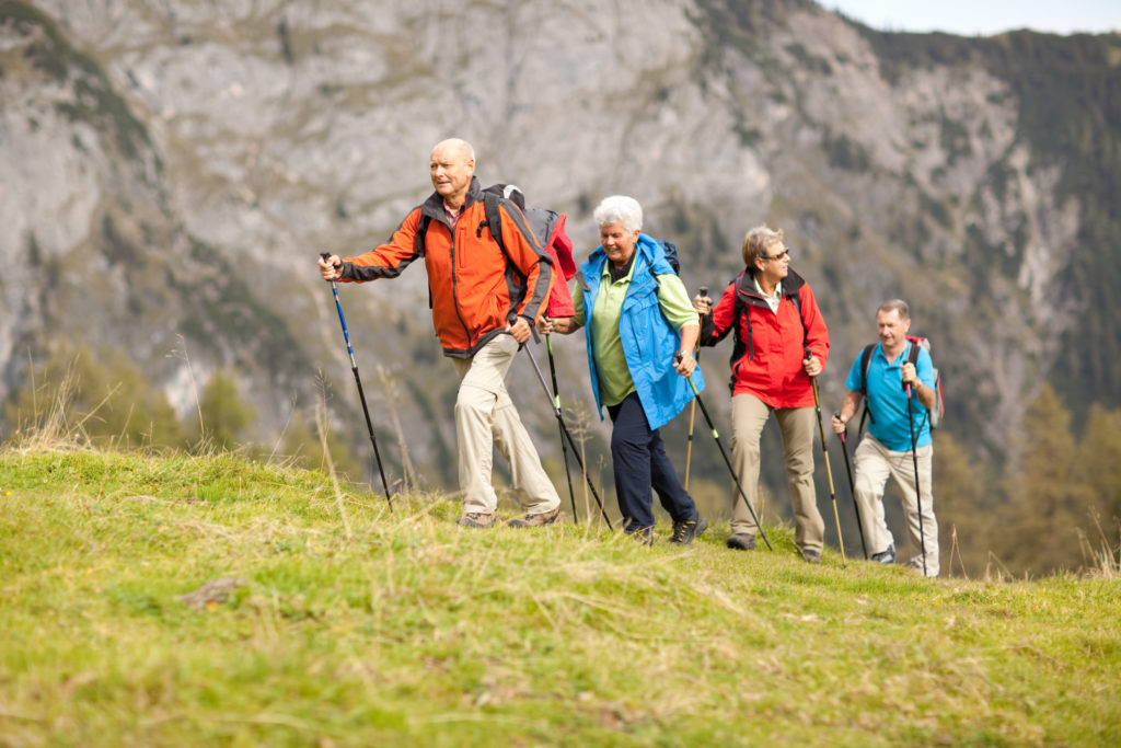 four senior hikers walking in a row