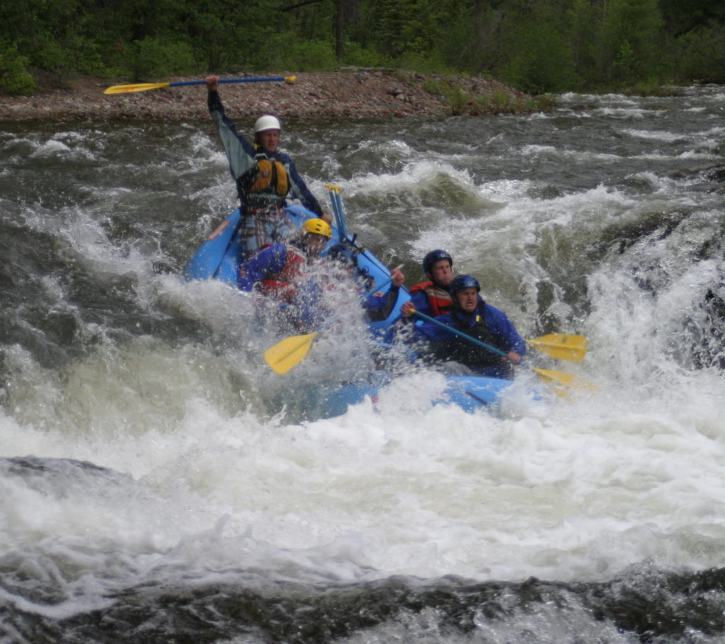 man cheers in a raft