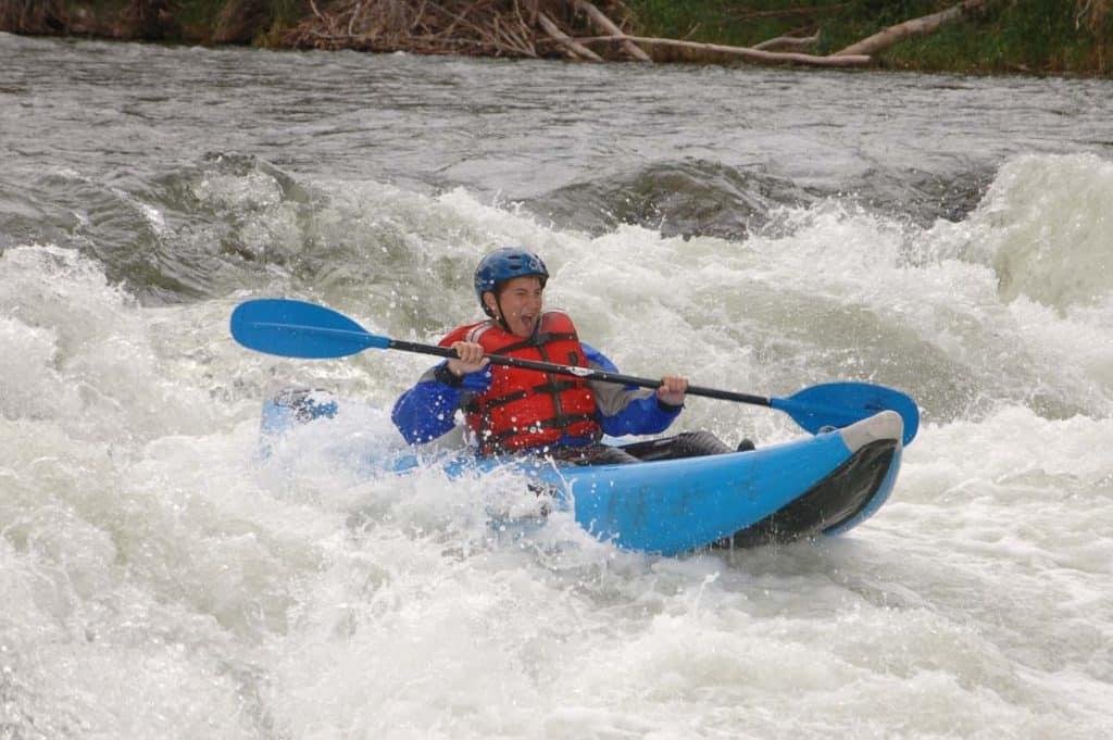 boy takes on waves in kayak